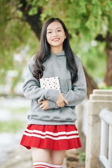 Portrait of happy smiling asian schoolgirl holding journal or diary and  when standing in park