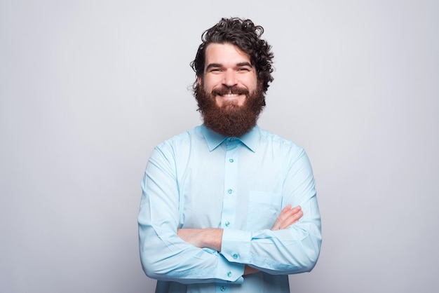 Portrait of happy smiling bearded man in blue shirt with crossed arms