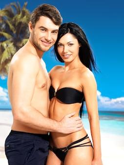 Ritratto di belle coppie sorridenti felici nell'amore alla spiaggia tropicale