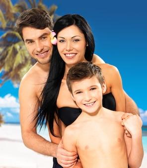 Ritratto di bella famiglia sorridente felice con il bambino alla spiaggia tropicale