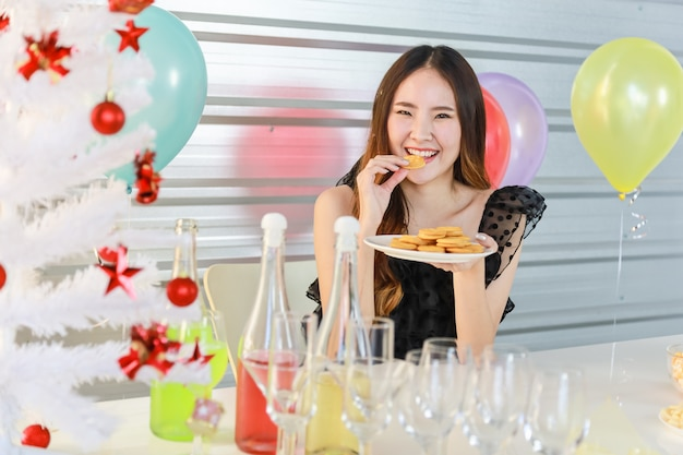 Portrait of happy and smiling beautiful young asian woman holding and eating cookie in xmas party with food and drink