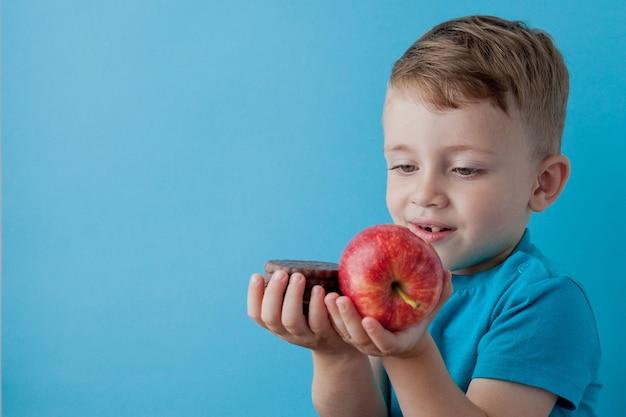 Портрет счастливый, улыбающийся мальчик, выбирающий нездоровую пищу