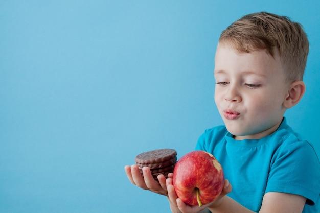 Портрет счастливый, улыбающийся мальчик, выбирая нездоровую пищу.