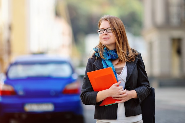 Portrait of happy smiling business woman with red folder in city