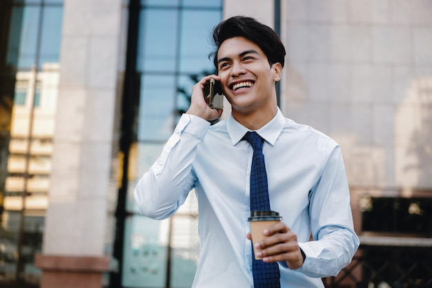 Portrait of a happy smiling businessman talking on mobile phone in the urban city. lifestyle of modern people.