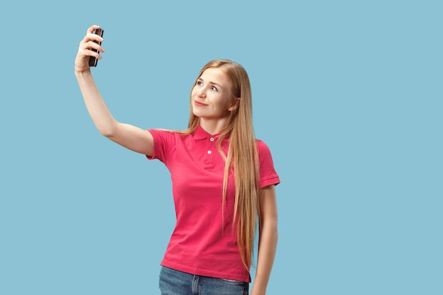 Portrait of a happy smiling casual girl showing blank screen mobile phone isolated over blue background