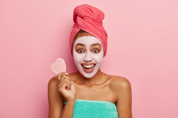 Portrait of happy smiling dark skinned woman applies mud mask, has rejuvenation treatment, holds sponge for removal makeup, has overjoyed expression