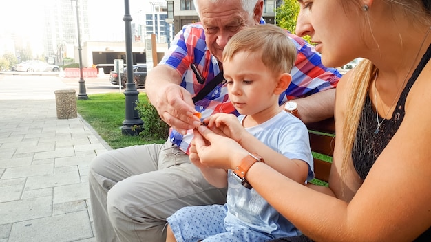 Portrait of happy smiling family with little toddler boy, young mather and grandfather sitting on bench at park and playing with small plastic toy