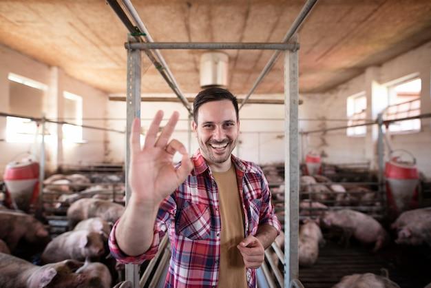 Ritratto di contadino sorridente felice che mostra segno giusto all'allevamento di suini