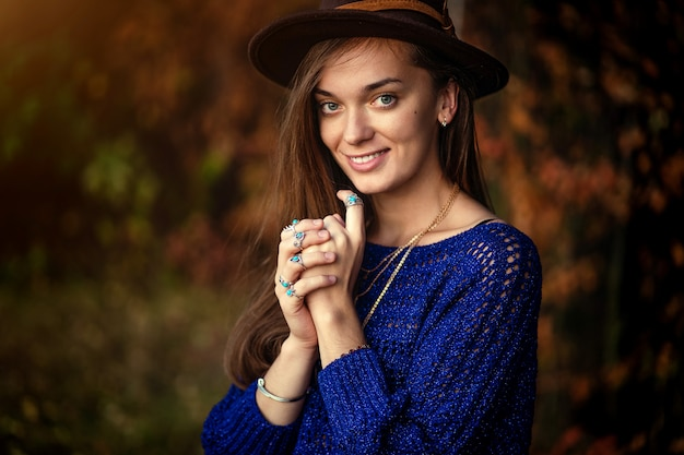 Portrait of happy smiling fashionable boho chic woman in hat and knitted blue sweater with necklace wearing silver rings with turquoise stone in autumn forest. stylish jewelry girl with boho fashion