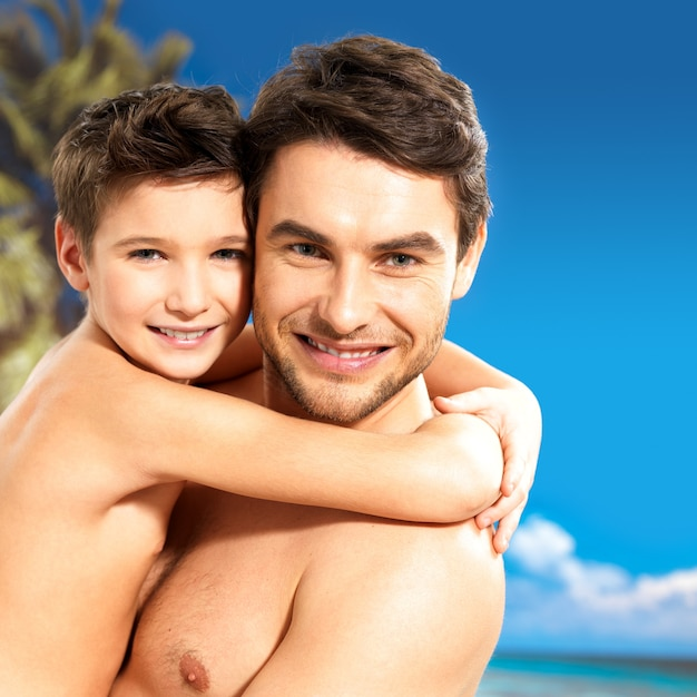 Portrait of happy smiling father hugs son 8 years old at tropical beach