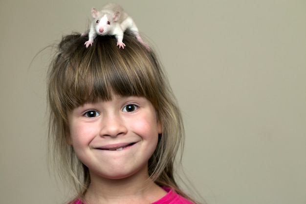 Portrait of happy smiling funny cute child girl with white pet mouse hamster on head on light wall copy space surface. keeping pets at home, care and love to animals concept.