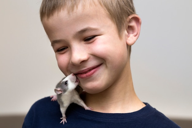 Portrait of happy smiling funny cute handsome child boy with white pet mouse hamster on shoulder on light copy space surface. keeping pets at home, care and love to animals concept.