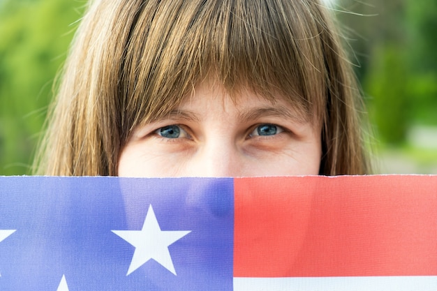 Portrait of happy smiling girl hiding her face behind usa national flag. international day of democracy concept.