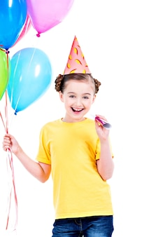 Portrait of happy smiling girl in yellow t-shirt holding colorful balloons - isolated on a white