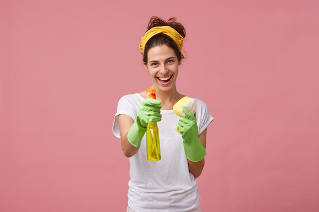 Portrait of happy smiling maid in white tidy t-shirt and green protective gloves demonstrating her detergent and sponge before work. people, housework, housekeeping and housecleaning concept