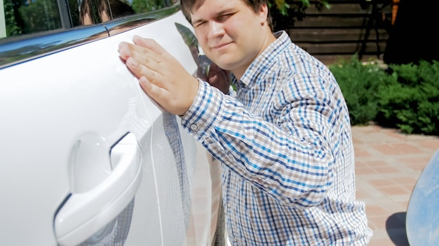 Portrait of happy smiling male driver looking on his new car and holding hand on door.