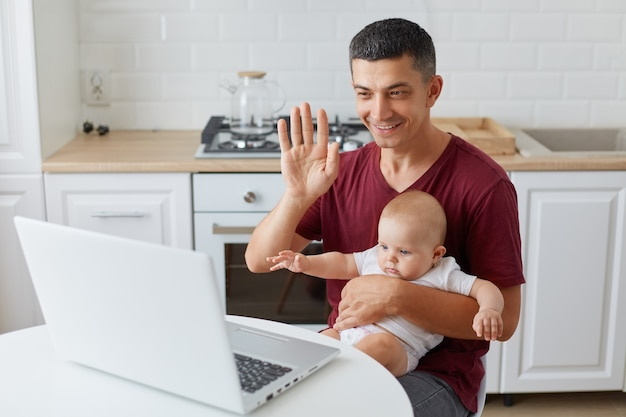 Portrait of happy smiling man sitting at table in kitchen in front of laptop computer, broadcasting livestream at his father's blog, waving had, saying hello to followers.