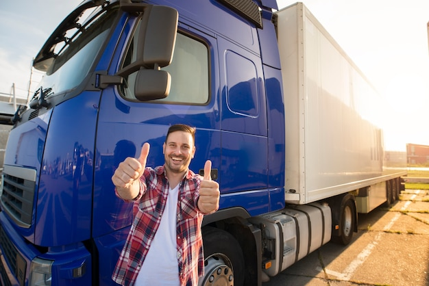 Portrait of happy smiling middle aged truck driver standing by his truck and holding thumbs up.