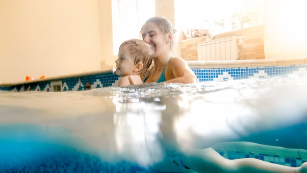 Portrait of happy smiling mother with 3 years old little son swimming in the pool at gym. family raelaxing, having fun and playing in water