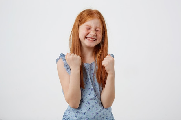 Portrait of happy smiling petite freckles red-haired girl, lwears in bluet, stands over white background with fists up.