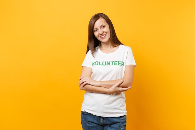 Portrait of happy smiling satisfied woman in white t-shirt with written inscription green title volunteer isolated on yellow background. voluntary free assistance help, charity grace work concept.