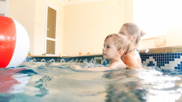 Portrait of happy smiling toddler boy playing with inflatable colorful beach ball with mother in indoors swimming pool