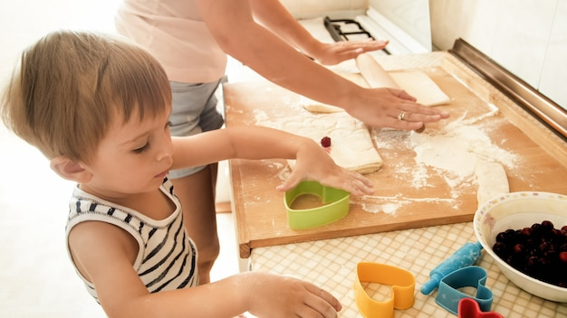 Portrait of happy smiling toddler boy with young mother baking and cooking on kitchen