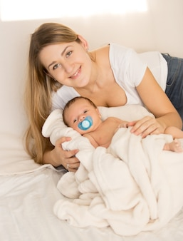 Portrait of happy smiling woman lying with her newborn baby on bed