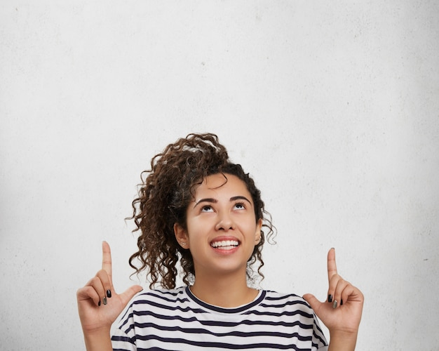 Portrait of happy smiling woman points with both hands up, advertises something as stands
