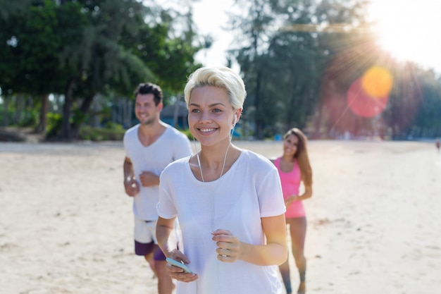 Portrait of happy smiling woman running on beach