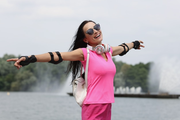 Portrait of happy smiling woman in sunglasses on background of fountain summer walking concept