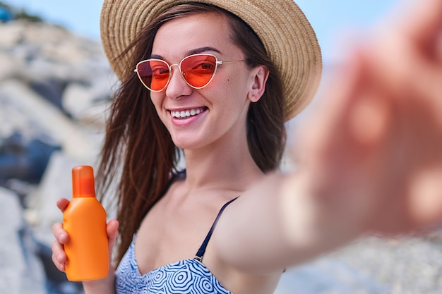 Portrait of a happy smiling woman in a swimsuit, straw hat and bright red glasses with a bottle of sun block cream during sunbathing by the sea in sunny weather in the summertime