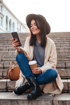 Portrait of a happy smiling woman texting on mobile phone