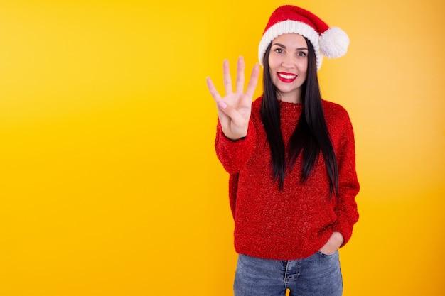 Portrait happy, smiling woman wearing x'mas santa hat, showing four fingers.