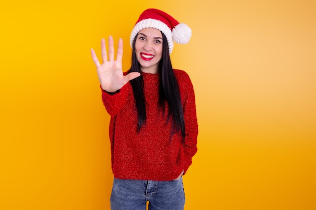 Portrait happy, smiling woman wearing x'mas santa hat, showing one fingers.