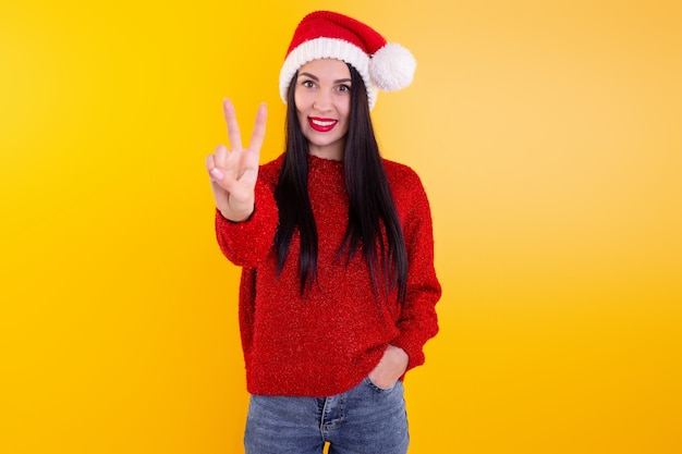 Portrait happy, smiling woman wearing x'mas santa hat, showing two fingers. christmas discount content.