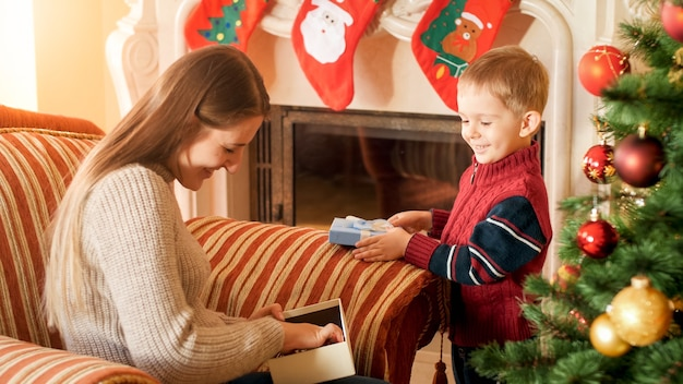 Portrait of happy smiling woman with her little son opens gift box on christmas morning at living room