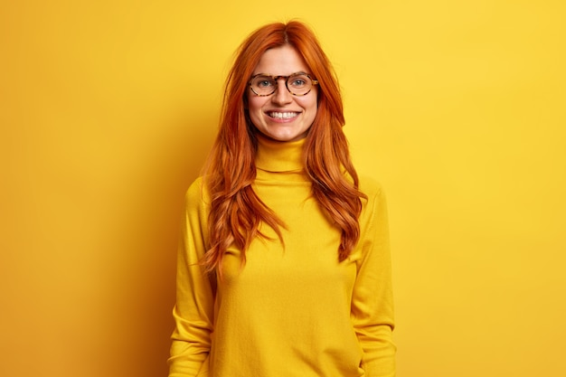 Portrait of happy smiling woman with red hair stays always positive enjoys funny talk with friend dressed in turtleneck and spectacles.