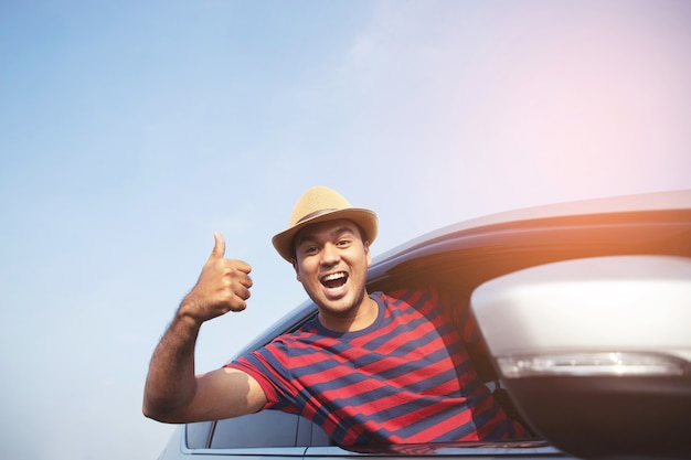 Portrait of happy smiling young asian man traveler on the road showing thumbs up while driving in his car.