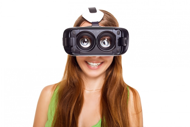 Portrait of happy smiling young beautiful girl getting experience using vr-headset glasses of virtual reality, big eyes, funny style, isolated