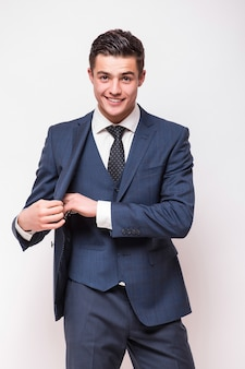 Portrait of happy smiling young businessman in blue suit isolated on white wall
