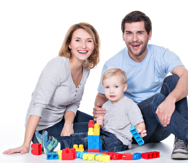 Portrait of happy smiling young parents playing with a baby - isolated on white