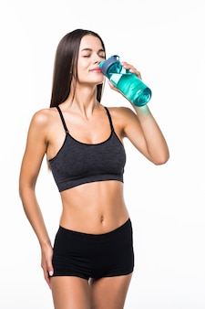 Portrait of happy smiling young woman in fitness wear with bottle of water, isolated on white