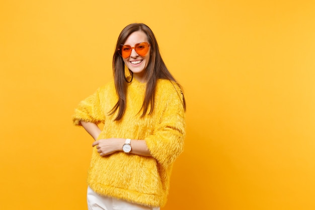 Portrait of happy smiling young woman in fur sweater, white pants, heart orange eyeglasses standing isolated on bright yellow background. people sincere emotions, lifestyle concept. advertising area.