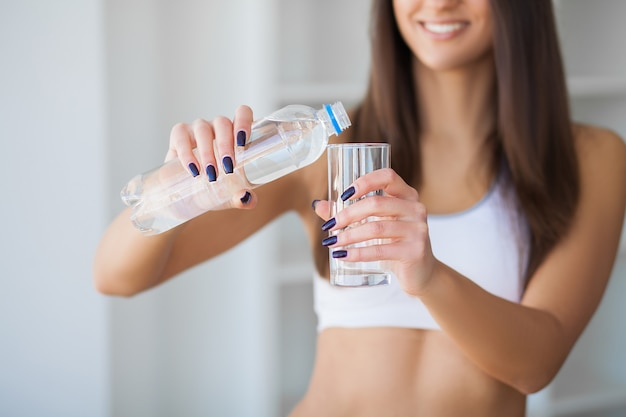 Portrait of happy smiling young woman with bottle of fresh water
