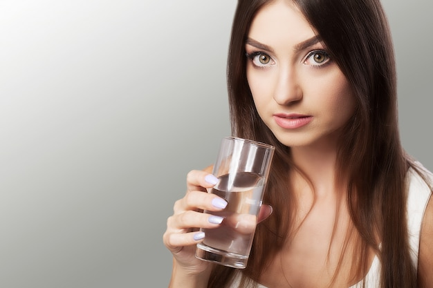 Portrait of happy smiling young woman with glass of fresh water