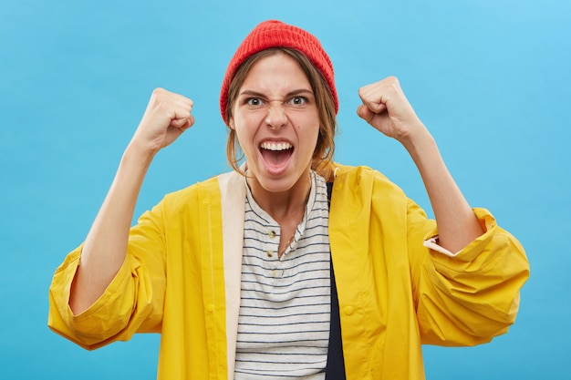 Portrait of happy successful young caucasian woman winner wearing red hat and yellow raincoat rejoicing over victory, success or good positive news with clenched fists, cheering, screaming in joy