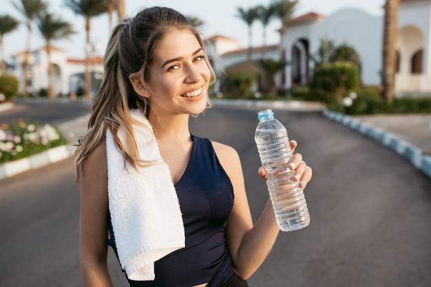 熱帯都市の通りに水のボトルを浮かべて陽気なアクティブな若い女性の肖像画幸せな晴れた朝。トレーニング、ワークアウト、健康的なライフスタイル、陽気な気分
