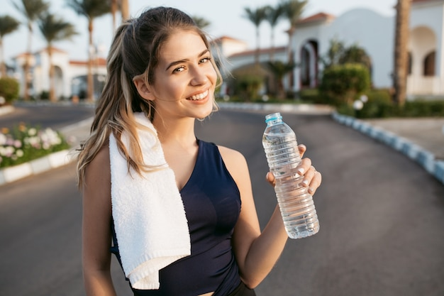 Portrait happy sunny morning of sportive active young woman smiling with bottle of water on street of tropical city. training, workout, healthy lifestyle, cheerful mood